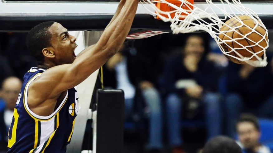 CORRECTS TO ALEC BURKS, NOT EARL WATSON - Utah Jazz's Alec Burks dunks in the second half of an NBA basketball game against the Minnesota Timberwolves, Wednesday, Feb. 13, 2013 in Minneapolis. The Jazz won 97-93. (AP Photo/Jim Mone)
