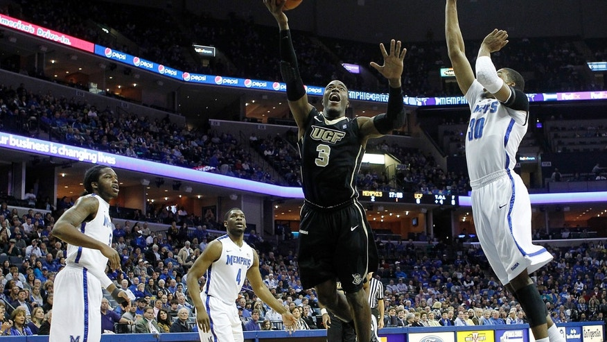 Central Florida guard Isaiah Sykes (3) goes to the basket against Memphis defenders Shaq Goodwin (5), Adonis Thomas (4) and D.J. Stephens (30) in the first half of an NCAA college basketball game on Wednesday, Feb. 13, 2013, in Memphis, Tenn. (AP Photo/Lance Murphey)
