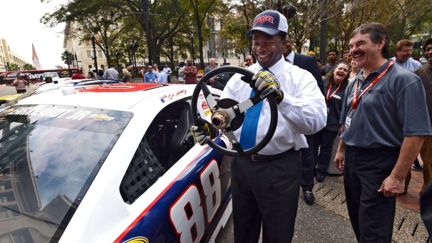Jacksonville Mayor Alvin Brown pretends to drive the No. 88 Chevrolet SS of Dale Earnhardt Jr., during NASCAR day Tuesday, Feb. 12, 2013, in Jacksonville, Fla.  The event is part a multi-city media blitz introducing the 2013 NASCAR Sprint Cup Series Chevrolet SS, Ford Fusion and Toyota Camry race cars.  (AP Photo/The Florida Times-Union, Bob Mack) MAGS OUT. TV OUT