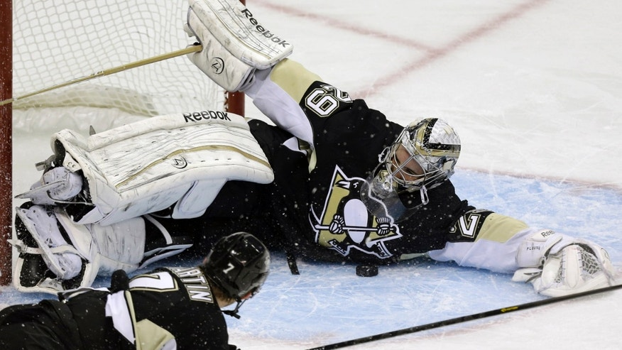Pittsburgh Penguins goalie Marc-Andre Fleury (29) makes a sprawling save with the help of defenseman Paul Martin (7) during the first period of an NHL hockey game against the Ottawa Senators in Pittsburgh on Wednesday, Feb. 13, 2013. (AP Photo/Gene J. Puskar)