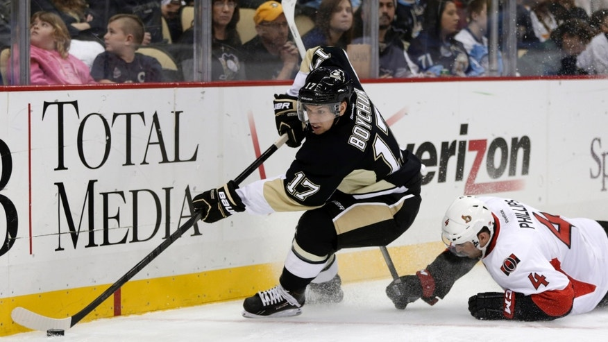 Pittsburgh Penguins center Zach Boychuk (17) passes the puck from the corner after colliding with Ottawa Senators defenseman Chris Phillips (4) during the second period of an NHL hockey game in Pittsburgh on Wednesday, Feb. 13, 2013. (AP Photo/Gene J. Puskar)