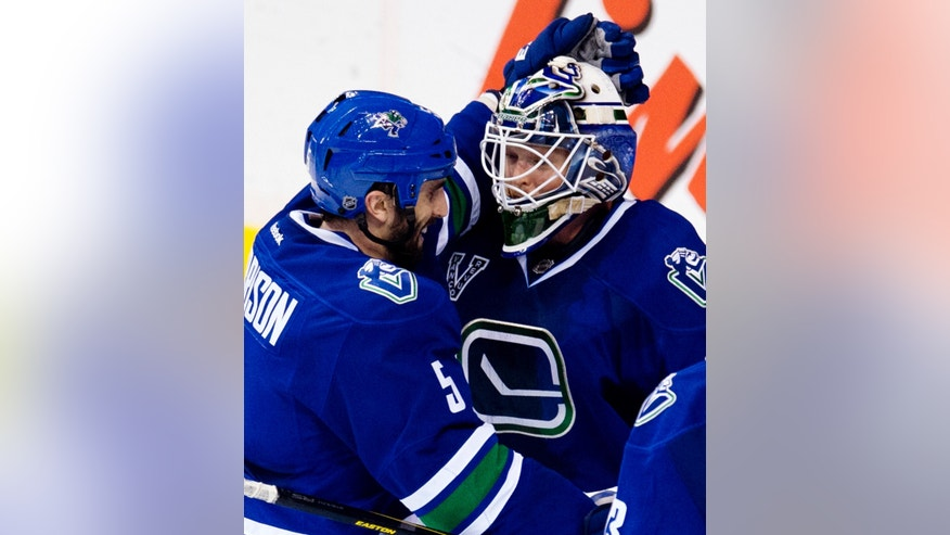 Vancouver Canucks defenseman Jason Garrison (5) celebrates their 5-1 win over the Calgary Flames with goalie Cory Schneider (35) after their NHL hockey game, Saturday, Feb. 9, 2013, in Vancouver, British Columbia. (AP Photo/The Canadian Press, Jonathan Hayward)