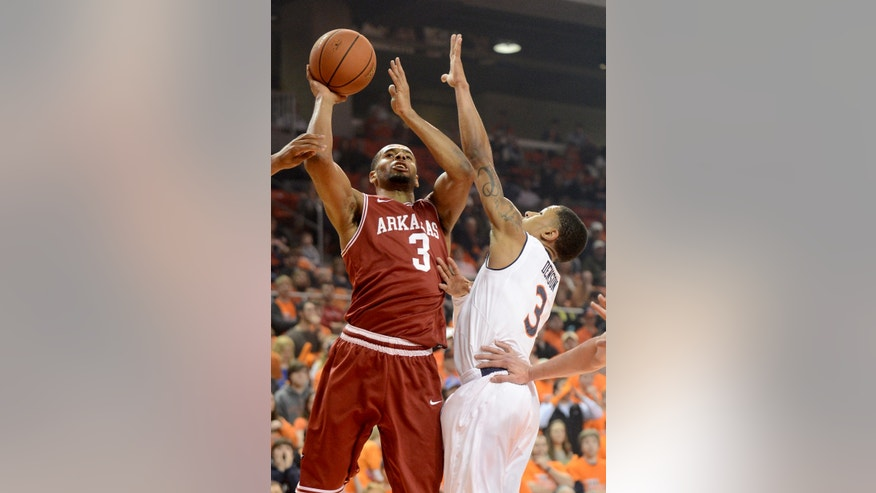 Arkansas' Rickey Scott, left, shoots over Auburn's Chris Denson, right, during an NCAA college basketball game on Wednesday, Feb. 13, 2013, at Auburn Arena in Auburn, Ala. (AP Photo/al.com, Julie Bennett)  MAGAZINES OUT