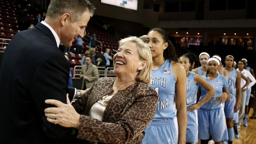 ADVANCE FOR WEEKEND EDITIONS, FEB. 16-17 - FILE - In this Feb. 7, 2013, file photo, North Carolina coach Sylvia Hatchell is congratulated by Boston College coach Erik Johnson after recording her 900th career coaching win, in North Carolina's 80-52 win over Boston College in an NCAA college basketball game in Boston. (AP Photo/Winslow Townson, File)