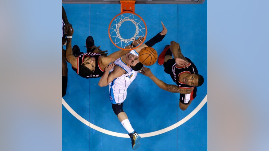 New Orleans Hornets guard Greivis Vasquez (21) drives to the basket between Portland Trail Blazers' Nicolas Batum, left, and guard Damian Lillard during the first half of an NBA basketball game in New Orleans, Wednesday, Feb. 13, 2013. (AP Photo/Gerald Herbert)