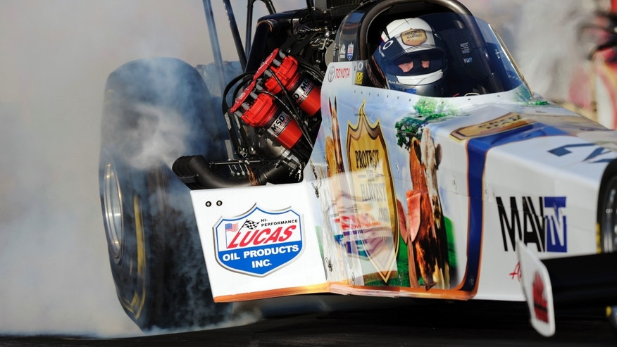 In this photo provided by NHRA, Top Fuel driver Brandon Bernstein performs a burnout in his dragster before launching down the track during the first NHRA auto racing qualifying session at Auto Club Raceway, Thursday, Feb. 14, 2013, in Fontana, Calif. (AP Photo/NHRA, Jerry Foss)