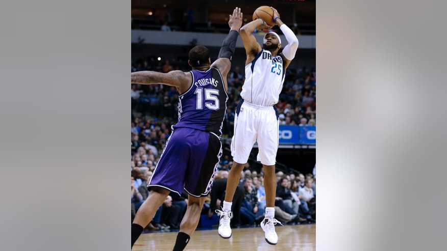 Dallas Mavericks' Vince Carter (25) shoots a 3-point basket as Sacramento Kings' DeMarcus Cousins (15) defends in the second half of an NBA basketball game Wednesday, Feb. 13, 2013, in Dallas. The Mavericks won 123-100. (AP Photo/Tony Gutierrez)