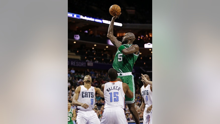 Boston Celtics' Kevin Garnett (5) shoots over Charlotte Bobcats' Kemba Walker (15) and Gerald Henderson (9) during the second half of an NBA basketball game in Charlotte, N.C., Monday, Feb. 11, 2013. The Bobcats won 94-91. (AP Photo/Chuck Burton)