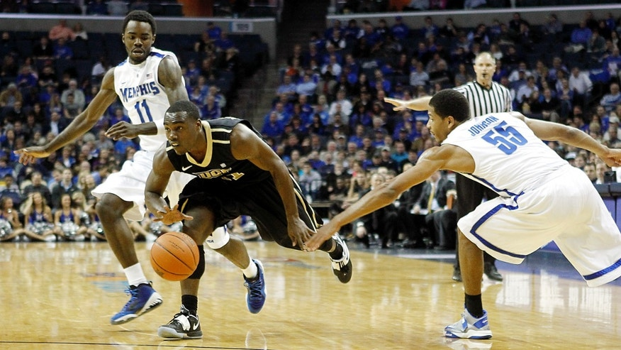 Central Florida guard Calvin Newell (11) takes the ball downcourt against Memphis guards Damien Wilson (11) and Geron Johnson (55 )in the first half of an NCAA college basketball game on Wednesday, Feb. 13, 2013, in Memphis, Tenn. (AP Photo/Lance Murphey)
