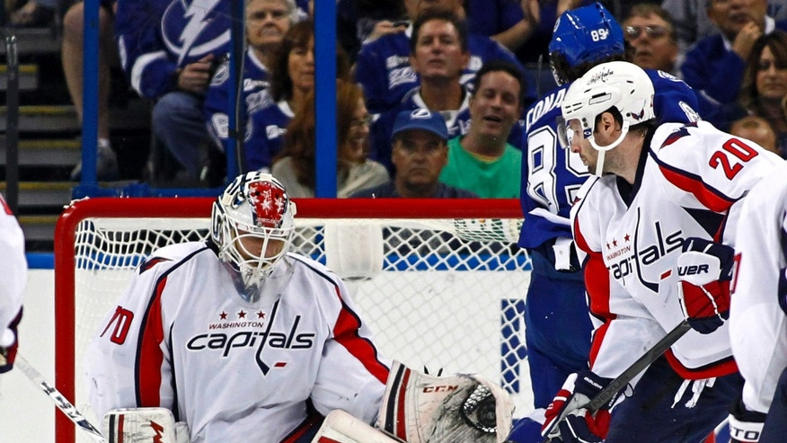 Washington Capitals goalie Braden Holtby, left, makes a save in front of teammate Troy Brouwer (20) and Tampa Bay Lightning's Cory Conacher during the first period of an NHL hockey game on Thursday, Feb. 14, 2013, in Tampa, Fla. (AP Photo/Mike Carlson)