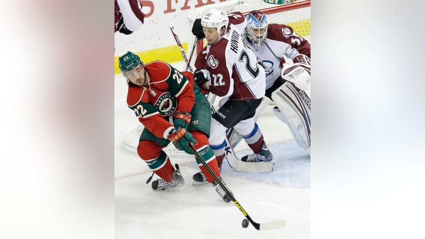Minnesota Wild's Cal Clutterbuck, left, tries to control the puck as Colorado Avalanche's Matt Hunwick, center, and goalie Jean-Sebastien Giguere defend in the first period of an NHL hockey game on Thursday, Feb. 14, 2013, in St. Paul, Minn. (AP Photo/Jim Mone)