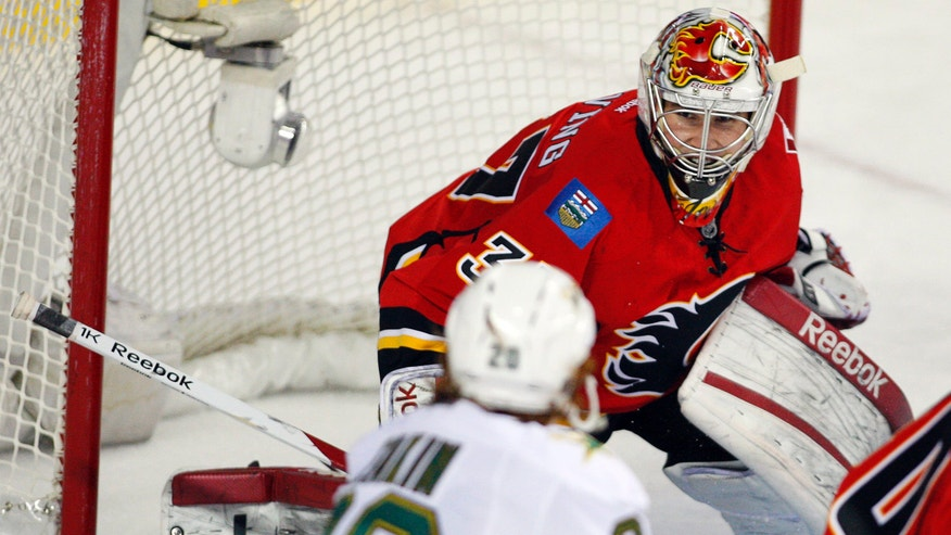 Dallas Stars' Cody Eakin, bottom, pressures Calgary Flames goalie Leland Irving during the second period of their NHL hockey game, Wednesday, Feb. 13, 2013, in Calgary, Alberta. (AP Photo/The Canadian Press, Jeff McIntosh)