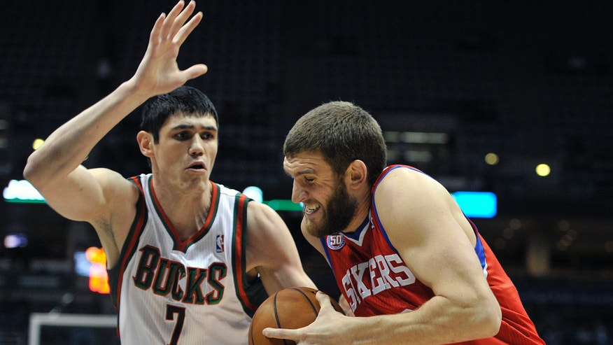 Milwaukee Bucks' Ersan Ilyasova (7) defends as Philadelphia 76ers' Spencer Hawes drives to the basket during the first half of an NBA basketball game on Wednesday, Feb. 13, 2013, in Milwaukee. (AP Photo/Jim Prisching)