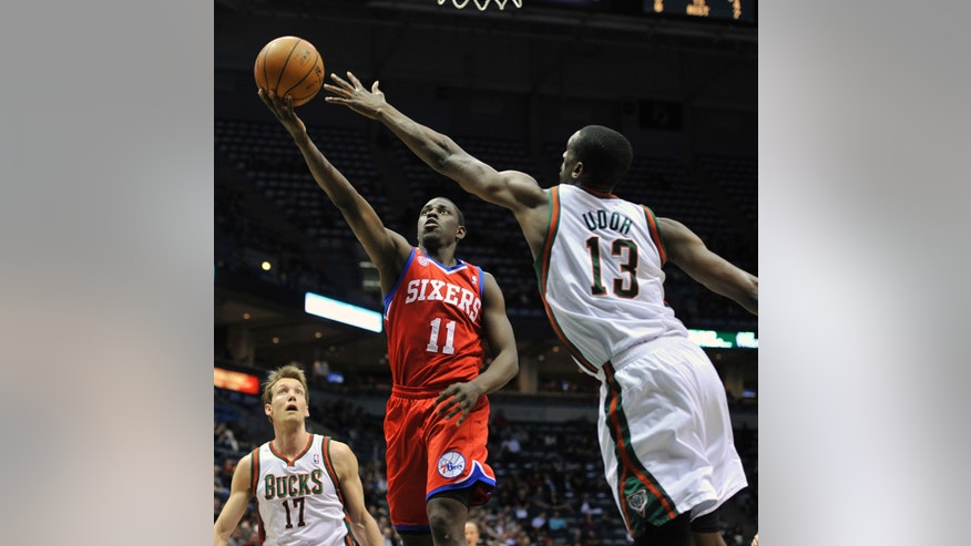 Milwaukee Bucks' Mike Dunleavy (17) and Ekpe Udoh (13) defend as Philadelphia 76ers' Jrue Holiday (11) drives to the basket during the first half of an NBA basketball game on Wednesday, Feb. 13, 2013, in Milwaukee. (AP Photo/Jim Prisching)