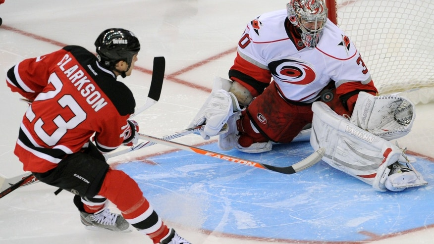 Carolina Hurricanes goaltender Cam Ward, right, stops a shot by New Jersey Devils David Clarkson during the third period of an NHL hockey game Tuesday, Feb. 12, 2013, in Newark, N.J. The Hurricanes won 4-2. (AP Photo/Bill Kostroun)