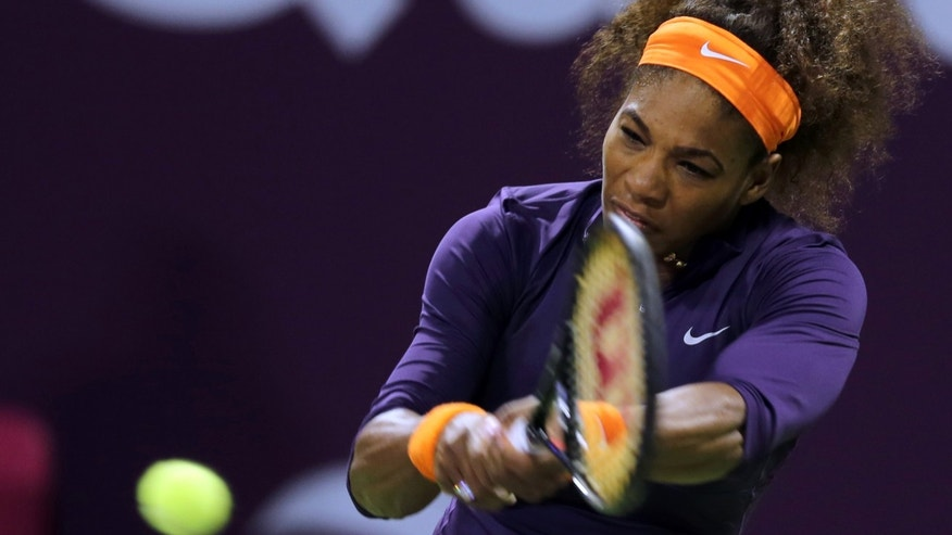 Serena Williams of the U.S. returns the ball to Poland's Urszula Radwanska on the fourth day of the WTA Qatar Ladies Open tennis tournament in Doha, Qatar, Thursday, Feb. 14, 2013. (AP Photo/Osama Faisal)