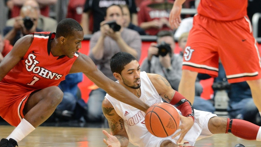 St. John's Phil Greene IV, left, reaches for a loose ball in front of Louisville's Peyton Siva during the first half of an NCAA college basketball game, Thursday, Feb. 14, 2013, in Louisville, Ky. (AP Photo/Timothy D. Easley)