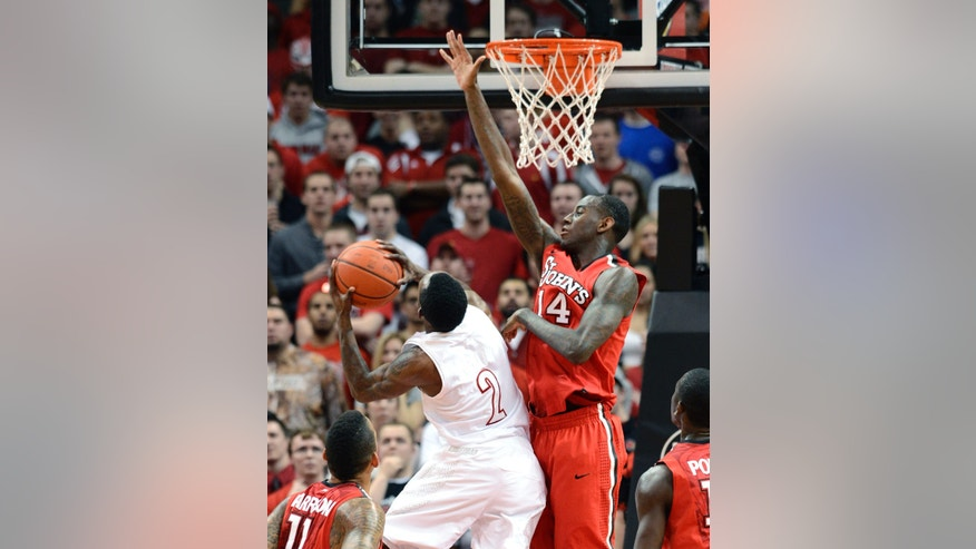 St. John's JaKarr Sampson, center, attempts to block the shot of Louisville's Russ Smith during the first half of an NCAA college basketball game Thursday, Feb. 14, 2013, in Louisville, Ky. (AP Photo/Timothy D. Easley)