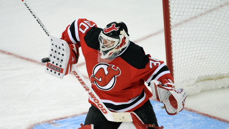 New Jersey Devils goaltender Martin Brodeur deflects the puck during the second period of an NHL hockey game against the Philadelphia Flyers on Friday, Feb. 15, 2013, in Newark, N.J. (AP Photo/Bill Kostroun)