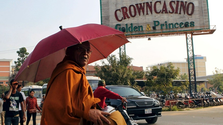 A Cambodian Buddhist monk takes a morning alms next to a casino signboard in Poipet, Cambodia Sunday, Dec. 9, 2012. Soccer betting is illegal in Cambodia, but visitors to this seedy frontier town wouldn't know it. In the rundown market where the smell of incense mixes with rotting garbage, betting goes on 24 hours a day inside shiny, glass-fronted parlors emblazoned with photos of famous European soccer players.  (AP Photo/Apichart Weerawong)