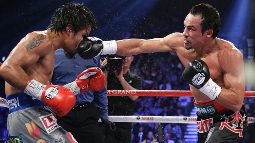 Dec. 8, 2012: Juan Manuel Marquez, right, lands a right to the head of Manny Pacquiao during their WBO world welterweight  fight in Las Vegas. Marquez won by a knockout. Pacquiao reportedly wants his next bout -- a fifth fight against Marquez -- to be held far away from Sin City and the United States' 39.6 federal tax rate. (AP)