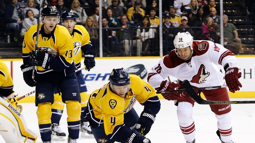 Nashville Predators defenseman Ryan Ellis (4) dives for the puck against Phoenix Coyotes left wing David Moss (18) in the first period of an NHL hockey game, Thursday, Feb. 14, 2013, in Nashville, Tenn. At left is Predators center Nick Spaling (13). (AP Photo/Mark Humphrey)