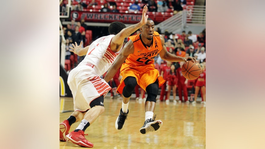 Oklahoma State's Markel Brown (22) drives against Texas Tech's Josh Gray during their NCAA college basketball game, Wednesday, Feb. 13, 2013, in Lubbock, Texas. (AP Photo/The Avalanche-Journal, Zach Long) ALL LOCAL TV OUT
