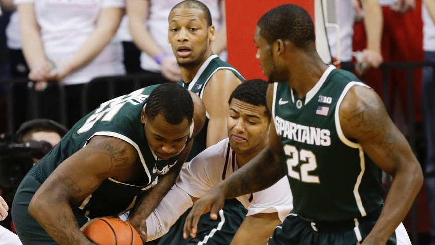 Michigan State's Derrick Nix, left, and Nebraska's Shavon Shields, center, struggle for the ball as Michigan State's Branden Dawson (22) and Adreian Payne, center rear, watch during the first half of an NCAA college basketball game in Lincoln, Neb., Saturday, Feb. 16, 2013. (AP Photo/Nati Harnik)