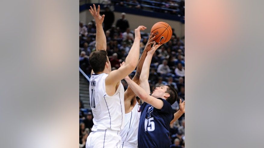 Villanova's Ryan Arcidiacono, right, drives to the basket while being guarded by Connecticut's Tyler Olander (10) and Omar Calhoun during the first half of an NCAA college basketball game in Hartford, Conn., Saturday, Feb. 16, 2013. (AP Photo/Fred Beckham)