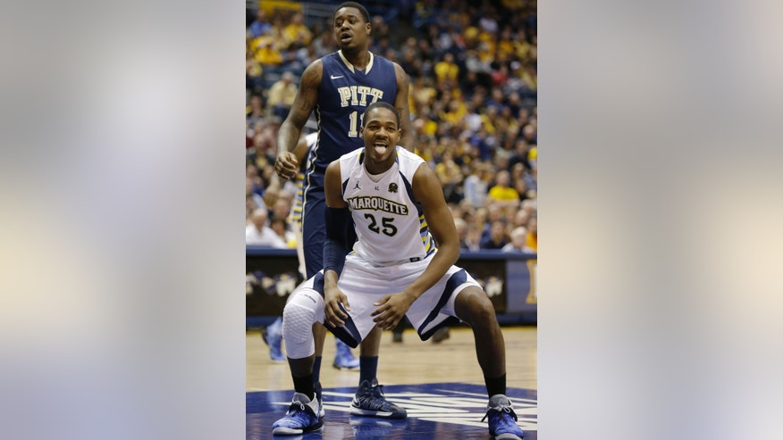 Marquette's Steve Taylor, Jr., (25) reacts in front of Pittsburgh's Dante Taylor (11) \during the first half of an NCAA college basketball game Saturday, Feb. 16, 2013, in Milwaukee. (AP Photo/Jeffrey Phelps)