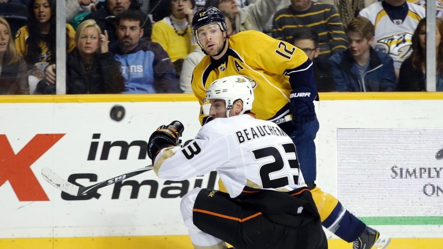 Nashville Predators center Mike Fisher (12) passes the puck past Anaheim Ducks defenseman Francois Beauchemin (23) during the second period of an NHL hockey game Saturday, Feb. 16, 2013, in Nashville, Tenn. (AP Photo/Mark Humphrey)