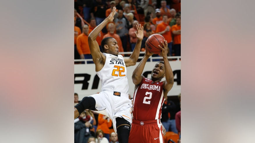 Oklahoma guard Steven Pledger (2) is fouled by Oklahoma State guard Markel Brown (22) as he shoots in the second half of an NCAA college basketball game in Stillwater, Okla., Saturday, Feb. 16, 2013. Oklahoma State won 84-79. (AP Photo/Sue Ogrocki)