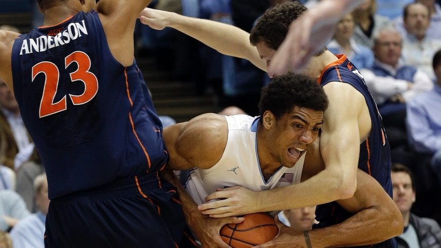 North Carolina's James Michael McAdoo is pressured by Virginia's Justin Anderson (23) and Evan Nolte, right, during the first half of an NCAA college basketball game in Chapel Hill, N.C., Saturday, Feb. 16, 2013. (AP Photo/Gerry Broome)