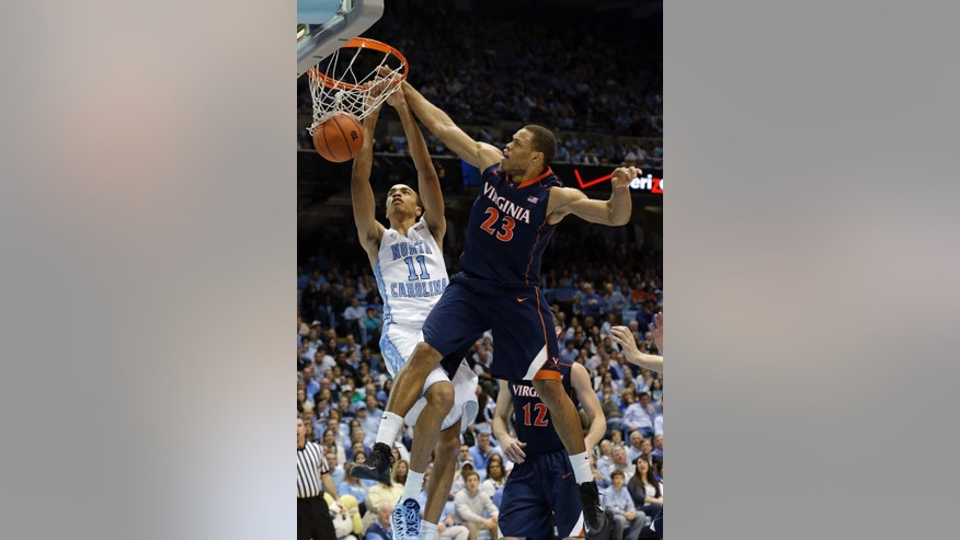 North Carolina's Brice Johnson (11) dunks as Virginia's Justin Anderson (23) defends during the first half of an NCAA college basketball game in Chapel Hill, N.C., Saturday, Feb. 16, 2013. (AP Photo/Gerry Broome)