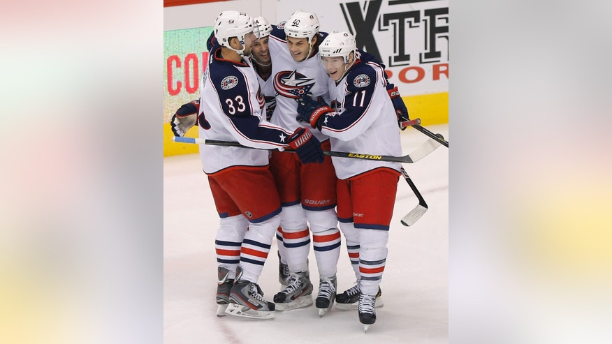 Columbus Blue Jackets' Derek MacKenzie celebrates his goal with teammates Adrian Aucoin (33), Matt Calvert (11) and Jared Boll (40) against the Phoenix Coyotes during the second period of an NHL hockey game, Saturday, Feb. 16, 2013, in Glendale, Ariz. (AP Photo/Matt York)