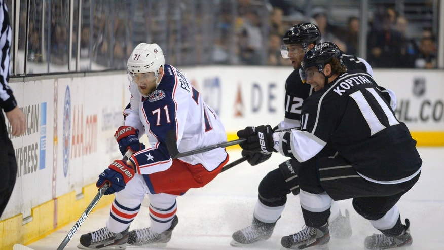 Columbus Blue Jackets left wing Nick Foligno, left, battles for the puck along with Los Angeles Kings left wing Simon Gagne, center, and center Anze Kopitar, of Slovenia, during the first period of their NHL hockey game on Friday, Feb. 15, 2013, in Los Angeles.  (AP Photo/Mark J. Terrill)