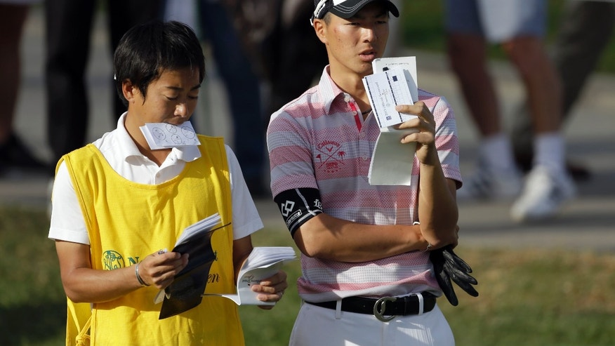 Ryo Ishikawa, right, of Japan, waits to tee off on the 10th tee in the second round of the Northern Trust Open golf tournament at Riviera Country Club in the Pacific Palisades area of Los Angeles, Friday, Feb. 15, 2013. (AP Photo/Reed Saxon)