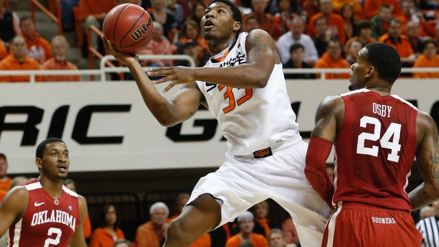 Oklahoma State guard Marcus Smart (33) shoots between Oklahoma guard Steven Pledger (2) and forward Romero Osby (24) in the first half of an NCAA college basketball game in Stillwater, Okla., Saturday, Feb. 16, 2013. (AP Photo/Sue Ogrocki)