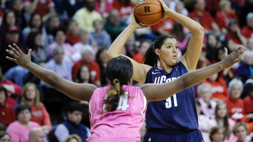 Connecticut's Stefanie Dolson (31) looks to make a pass as she is defended by Rutgers' Monique Oliver (34) during the first half of an NCAA college basketball game Saturday, Feb. 16, 2013, in Piscataway, N.J. (AP Photo/Mel Evans)