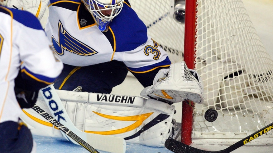 St. Louis Blues goalie Jake Allen grabs for the puck during first-period NHL hockey game action against the Calgary Flames in Calgary, Alberta, Friday, Feb. 15, 2013. (AP Photo/The Canadian Press, Jeff McIntosh)