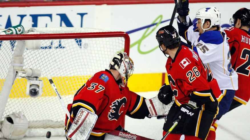 St. Louis Blues' Chris Stewart, second from right, celebrates his team's goal as Calgary Flames goalie Leland Irving, left, and Dennis Wideman look at the puck during first-period NHL hockey game action in Calgary, Alberta, Friday, Feb. 15, 2013. (AP Photo/The Canadian Press, Jeff McIntosh)