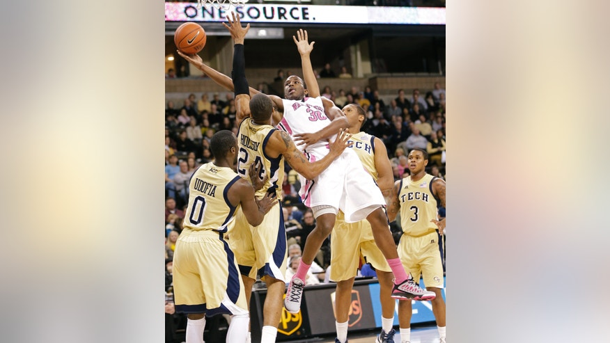 Wake Forest's Travis McKie (30) drives between Georgia Tech's Kammeon Holsey (24), Mfon Udofia (0), Marcus Georges-Hunt (3), and Julian Royal (1) during the first half of an NCAA college basketball game in Winston-Salem, N.C., Saturday, Feb. 16, 2013. (AP Photo/Chuck Burton)