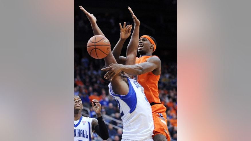 Syracuse's C.J. Fair passes the ball  as he runs into Seton Hall's Kevin Johnson during the first half of an NCAA college basketball game Saturday, Feb. 16, 2013, in Newark, N.J. (AP Photo/Bill Kostroun)