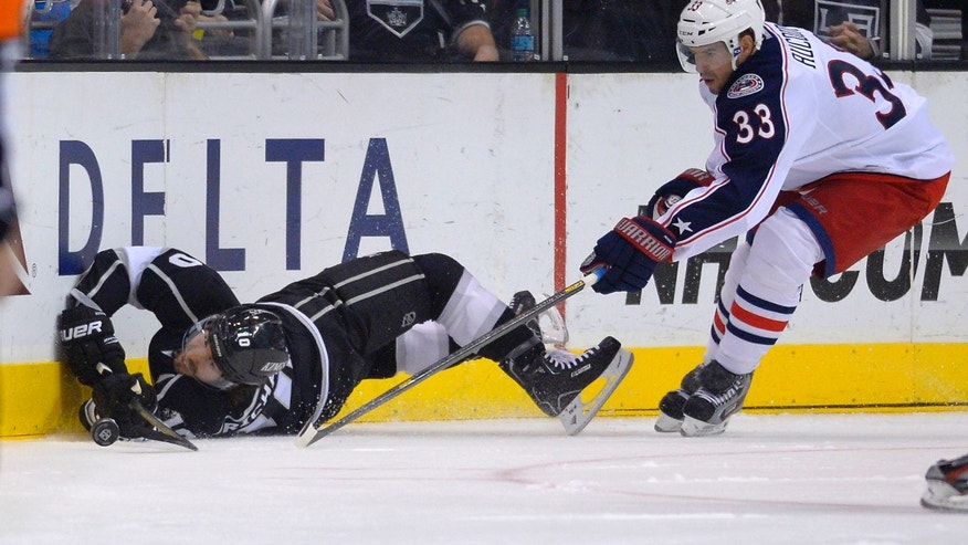 Los Angeles Kings center Mike Richards, left, falls as he goes for the puck along with Columbus Blue Jackets defenseman Adrian Aucoin during the first period of their NHL hockey game on Friday, Feb. 15, 2013, in Los Angeles. (AP Photo/Mark J. Terrill)