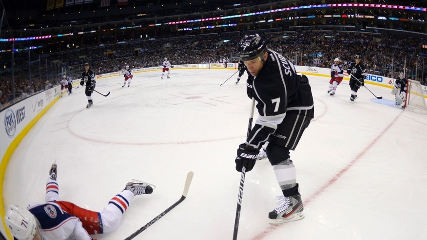 Columbus Blue Jackets left wing Nick Foligno, left, and Los Angeles Kings defenseman Rob Scuderi battle for the puck during the third period of their NHL hockey game, Friday, Feb. 15, 2013, in Los Angeles. The Kings won 2-1.  (AP Photo/Mark J. Terrill)