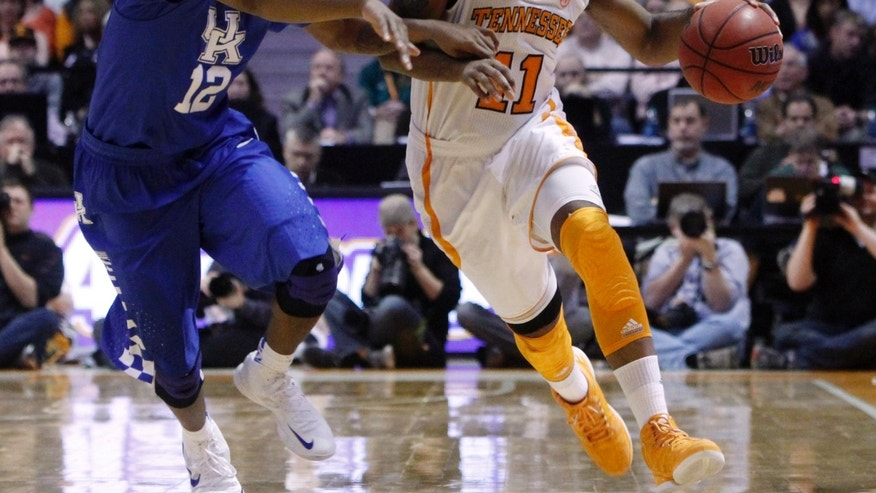 Tennessee guard Trae Golden (11) drives against Kentucky guard Ryan Harrow (12) in the second half of an NCAA college basketball game on Saturday, Feb. 16, 2013, in Knoxville, Tenn. Tennessee won 88-58. (AP Photo/Wade Payne)
