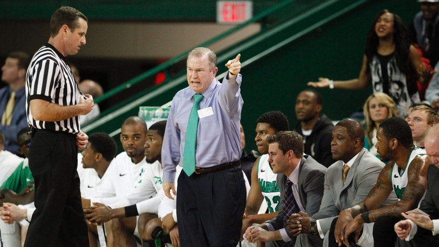 Marshall head coach Tom Herrion, center, contests a referee's call during the first half of an NCAA college basketball game against Memphis, Saturday, Feb. 16, 2013, at the Cam Henderson Center in Huntington, W.Va. (AP Photo/Randy Snyder)