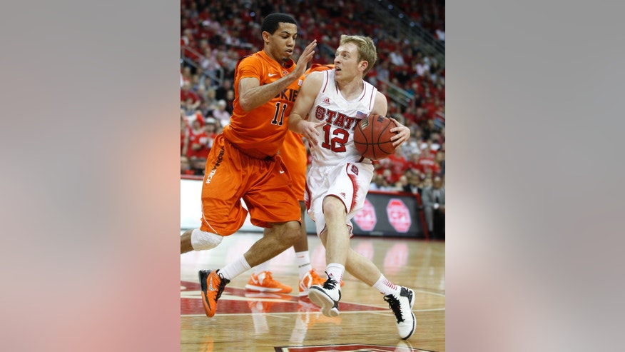 N.C. State's Tyler Lewis (12) drives around Virginia Tech's Erick Green (11) during the first half of an NCAA college basketball game in Raleigh, N.C., Saturday, Feb. 16, 2013. (AP Photo/The News & Observer, Ethan Hyman)  Mandatory Credit