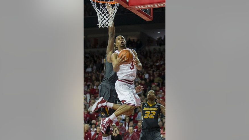 Arkansas' Rickey Scott (3) drives against Missouri's Earnest Ross (33) during the first half an NCAA college basketball game in Fayetteville, Ark., Saturday Feb. 16, 2013. (AP Photo/Gareth Patterson)
