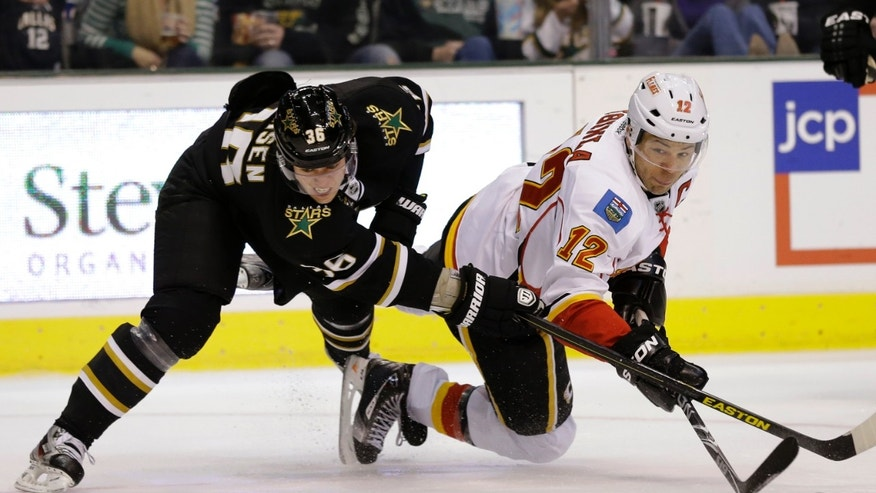 Dallas Stars' Philip Larsen (36) of Denmark and Calgary Flames' Jarome Iginla (12) compete for control of the puck in the second period of an NHL hockey game Sunday, Feb. 17, 2013, in Dallas. (AP Photo/Tony Gutierrez)